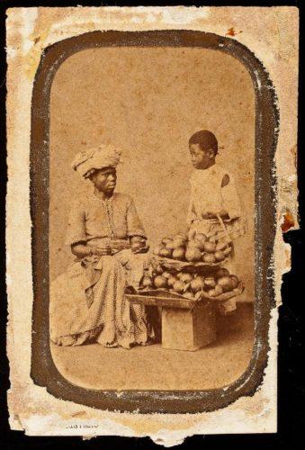 Caixa de Texto: Figura 3: Mulher negra carrega o tabuleiro e seu filho, século XIX. Fonte: Google Images.
